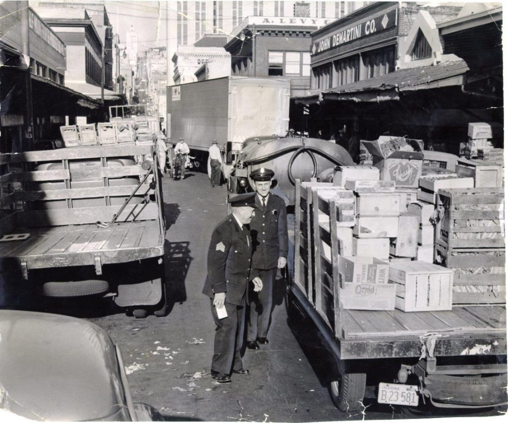 Two policemen issuing tickets to produce delivery trucks at Washington and Front streets, Aug. 15, 1956. Credit: SAN FRANCISCO HISTORY CENTER, SAN FRANCISCO PUBLIC LIBRARY